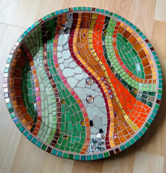 """My inspiration comes mainly from the infinite form, patterns & colours of nature. Nature's palette with a pinch of the abstract, Islamic geometry - bright, vibrant and usually lots of swirls! Designs incorporating glass and ceramic tiles, gemstones and beads,with an Islamic/Arabic influence. Beginners/intermediate mosaic workshops offered - please contact me for details.     [caption id=""""attachment_4658"""" align=""""alignnone"""" width=""""300""""] Community mosaic paving stone now installed in the Green Backyard gardens[/caption]     I have designed and coordinated several community mosaics in and around Peterborough. The biggest & most recent one being the Froglife mural, commissioned by the charity Froglife and installed at the Green Backyard on Oundle Rd. This 4ft by 8ft glass mosaic mural was created with the help of over 100 volunteers (most of whom were complete beginners in mosaic art) and took 5 months to complete through workshops held twice a week at The Green Backyard. It is situated on the back of a sheltered bench, beside the pond and depicts images of plants and animals found in and around the pond.  The mural represents a celebration of the community who came together, braving some of the coldest winter months, to create a masterpiece!   [caption id=""""attachment_4656"""" align=""""alignnone"""" width=""""600""""] The Froglife mural installed at The Green Backyard, Peterborough.[/caption]     Last year I was commissioned by the Uppingham In Bloom Committee to deliver a community mosaic project in Uppingham, Leicestershire. We designed and created a beautiful mosaic flower-covered stone plinth to commemorate and celebrate 35 years of the annual 'Uppingham in Bloom' event. This piece was installed in one of the flower beds in the town centre & Uppingham went on to win the East Midlands In Bloom Gold Award 2018"""