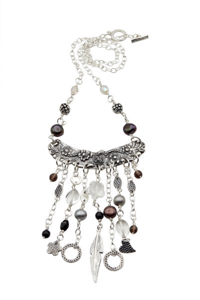 """[caption id=""""attachment_6016"""" align=""""alignleft"""" width=""""300""""] Silver tassel pendant on a snake chain[/caption]  I have always spent time making things. As a child I made doll's clothes after learning to knit and sew alongside my mother. As an adult I continued to make clothes, bags and jewellery. At Teacher Training College my personal study subject was ceramics. Skills I acquired back in the seventies are now in full use again in my work with metal clay.  I started making silver jewellery in 2009 when I embarked on a City & Guilds Silver Jewellery Making course. It wasn't long before I discovered silver metal clay. What an amazing material; I couldn't believe my luck - to be able to make pieces in clay, fire them and they turn into metal...fine silver. Wow! This material has inspired me!  I specialise in making free-form hollow beads and many of my pieces contain one or more of these bespoke beads. I use silver metal clay to make pendants and also charms for earrings and bracelets in conjunction with sterling silver wire and sheet.  I make jewellery that I would like to wear myself and what a joy to create striking individual pieces that others love too!  Take a look at https://www.peterboroughgiftshop.com/collections/lesley-adolphson-jewellery where you can see and purchase some of my work."""