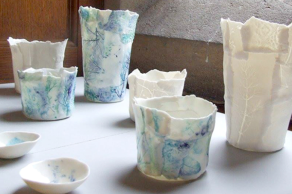 """[caption id=""""attachment_2111"""" align=""""alignleft"""" width=""""800""""] Delicate porcelains by Kathryn Parsons at the Yarrow Gallery, Oundle, August 2016. Photo: Tony Nero[/caption] A large collaborative exhibition of Artists and Artisans is being held at the Yarrow Gallery, Oundle 2nd - 7th August 2016, The exhibition will include new sculptural works as well as mosaic art, paintings, textile objects, and jewellery. Materials and artists will be on hand to help you create a work in response to the exhibition or try a medium you have not used before. Open Daily 10am – 4pm  Exhibition curated by Caroline Hawkins & Caroline Kisby  There is no charge for admission to the show.  [caption id=""""attachment_2114"""" align=""""alignright"""" width=""""600""""] Texiles at the Yarrow Gallery Aug 2016[/caption]  The Yarrow Gallery Building is an very beautiful space. Opened in 1918 on the first Oundle School Speech Day after the WW1 ended. It was funded by Mr AF Yarrow, later Sir Alfred, in memory of his son, Eric, who was killed on 8th May 1915 at Ypres.  Headmaster, FW Sanderson said: 'The object of the Museum is to make it possible to extend the work already begun in the Art Room.'In 1970 the building was adapted to create a permanent exhibition space, and the tradition of staging exhibitions of professional artists began.  During recent major restoration work, the display area was redesigned on the ground floor and the gallery upstairs was opened up to provide further exhibition space. It is now one of the most attractive galleries in East Anglia. At present there are five or six major exhibitions a year.    The Yarrow Gallery, Glapthorn Road, Oundle, PE8 4PS"""